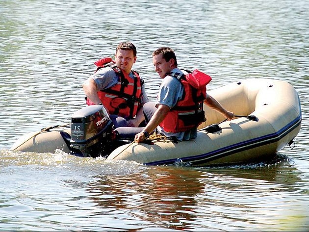 Hasiči na člunu prohledávají vodní hladinu.
