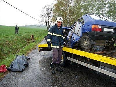 Jeden z hasičů pomáhá naložit nabouraný automobil.