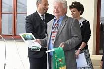 Starosta Jan Rejfek se zelenou stuhou, kterou městys Dešenice získal v soutěži Vesnice roku.