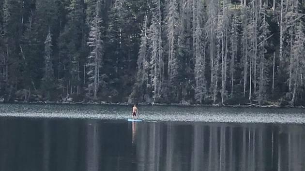 Muž na paddleboardu na ledovcovém  Černém jezeře na Šumavě.