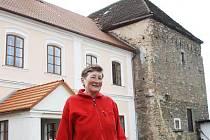Alena Valentová před secesním zámkem a starou tvrzí ve Svojšicích.
