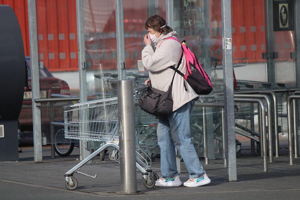 Do obchodů chodí většina lidí nyní s rouškami.