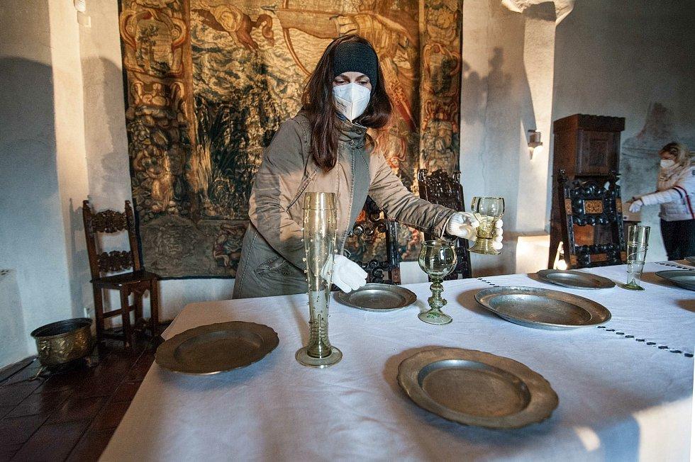 Příprava prostírání v hodovní místnosti s dobovým cínovým nádobím.