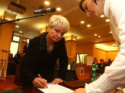Bývalá ministryně zdravotnictví Milada Emmerová právě podepisuje slib zastupitele, za pár okamžiků ji zastupitelé zvolí první hejtmankou v historiíi.