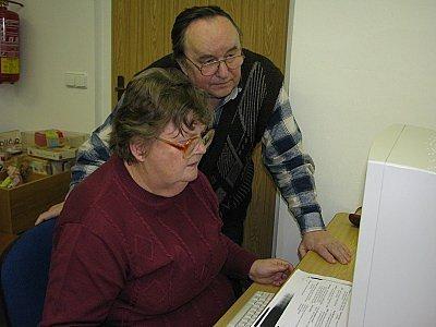 Senioři se učili s počítačem.