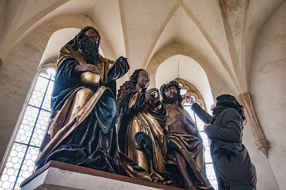 Oltářní gotické sochy v kapli se opatrně čistí od pavučin a prachu.