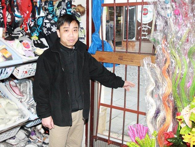 Vietnamský obchodník z Klatov ukazuje mříže ve dveřích, v nichž zůstala mladá zlodějka uvězněna.