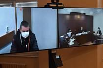 Soudní proces moderně, pomocí videokonference. Na obrazovce vlevo je obžalovaný sedící ve věznici v Plzni, vpravo je pohled do soudní síně v Klatovech.
