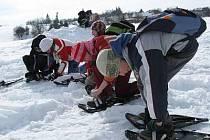 Účastníci akce DDM Horažďovice obouvají sněžnice před startem expedice.