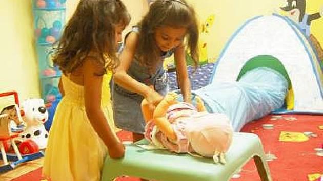 Děti, které bydlí v Domě sv. Zdislavy, si užívají léto v herně i na zahradě. Na snímku přebalují panenku Simonka a Ilonka.