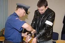 Eskorta sundavá u soudu pouta  Pavlu Strakovi, obžalovanému mimo jiné z vydírání.