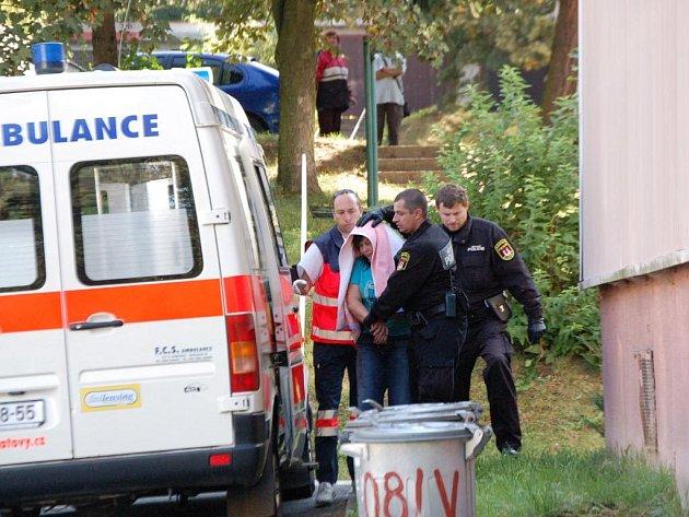 Po přistavění hasičského žebříku vlezou policisté a hasiči do bytu oknem a za chvíli ženu nakládají do sanitky.