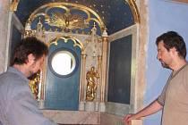 Kaple rodiny Stadionů na Klenové. Restaurátoři Jiří Stýblo (vlevo) a Jindřich  Šlechta opatrně vsouvají nově zrestaurovaný  oltář do okenního výklenku kaple.