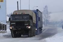 Někteří dopravci si pomáhají sami.  Kamion uvíznutý pod kopcem vytahuje veteránská tatra.