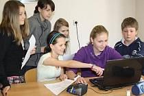 Žáci 7. B ZŠ Klatovy v Plánické ulici se radí nad stránkami svého třídního časopisu, který si sami vymysleli a udělali.