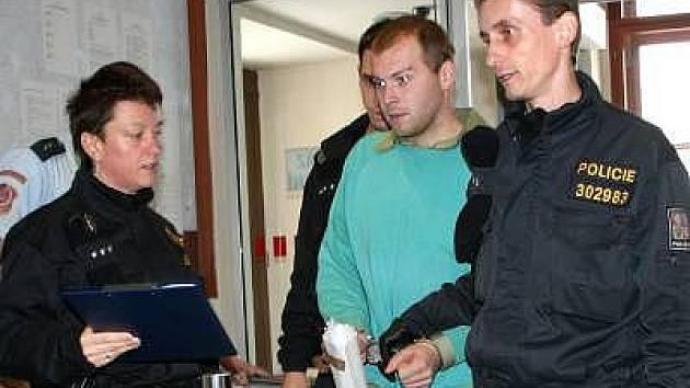 Policisté přivádějí k plzeňskému soudu mladíka obviněného z brutální vraždy stařenky v Klatovech.