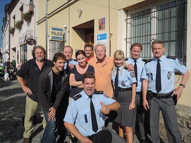 Režisér Jaroslav Soukup (uprostřed) pózuje se seriálovými policisty před skutečným policejním obvodním oddělením v Kašperských Horách.