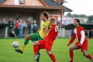 Velimský stoper Václav Antoš (v souboji vpravo) se snaží atakovat protihráče Týniště.