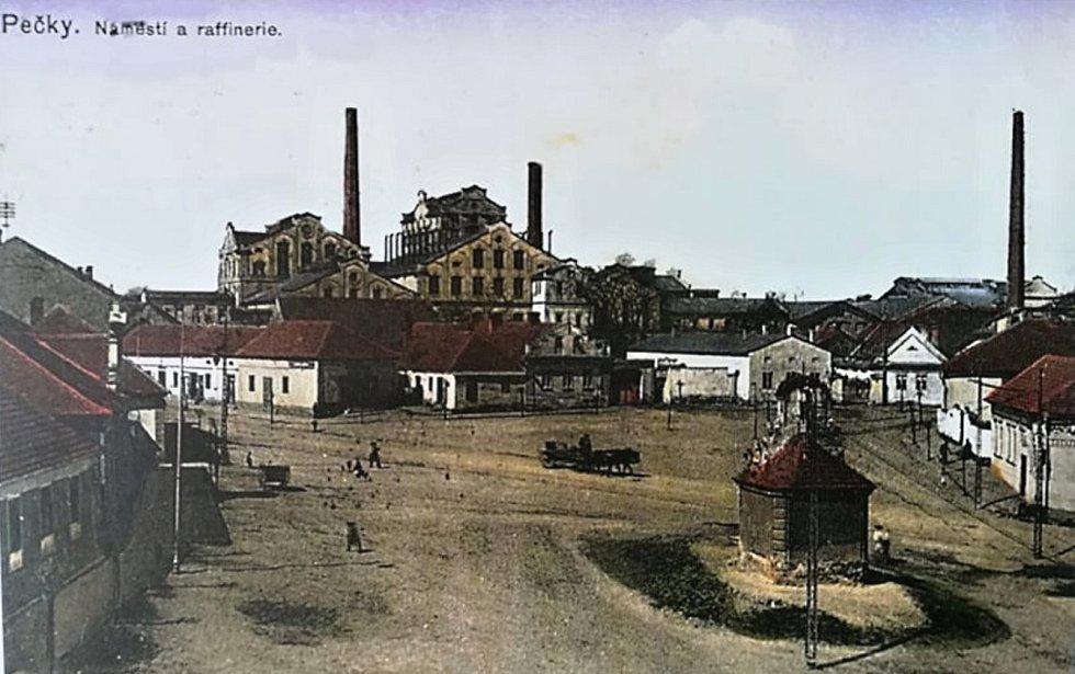 Pohlednice zachycuje centrum Peček - náměstí s pohledem na místní rafinérii.