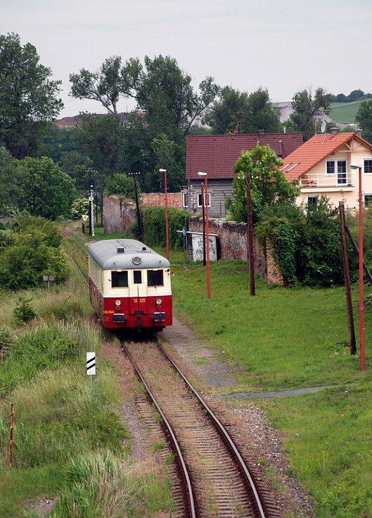 Motoráček z šedesátých let řady M 262.054 tzv. kredenc (přezdívku si vysloužil podle dřevěné stavby vozu a tvaru) přijíždí na zastávku Plaňany