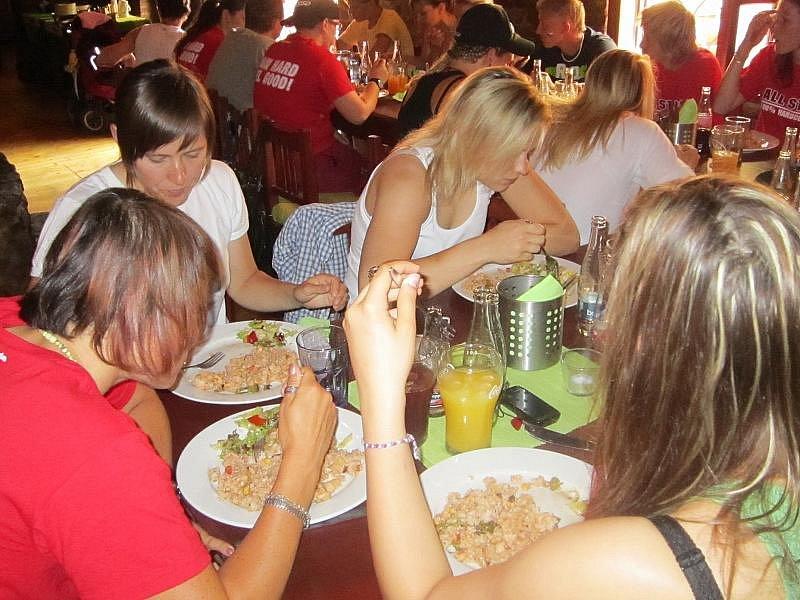 TÝMOVÝ OBĚD. Hráčky českého týmu Kateřina Flachsová (vlevo v bílém), Petra Šmardová (vlevo zezadu), Tereza Šťastná (vpravo) zezadu a Petra Melicheríková (v bílém tílku) na společném obědě.