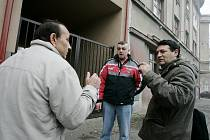 """Cyril Koky (vpravo) diskutuje s jedním z obyvatel domu v Zengrově ulici. Romští nájemníci ve většině případů před hledáčkem fotoaparátu utíkali a schovávali svoje děti. """"Foťte si Češi, né nás,"""" lamentovali."""