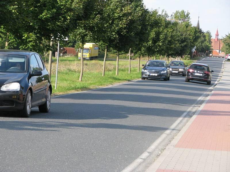 Silnice podél hřbitova u Červených Peček těsně před vjezdem do Nebovid.
