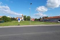 Provizorní parkovací plocha u supermarketu Tesco v Pečkách.