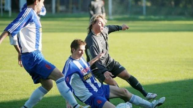 Pečky v přesile. Domácí fotbalisté Petr Hanuš (zleva) a Lukáš Martínek bojují o míč s Milanem Petrákem.