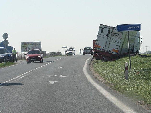 Řidič kamionu nedobrzdil za kolonou. Skončil v poli.