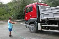 Řidič před výjezdem z lomu smývá prach.