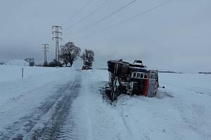 Na silnici mezi obcemi Zdislavice a Malovidy skončil kamion na boku. A o pár metrů dál i sypač, který se snažil vozovku zprůjezdnit.