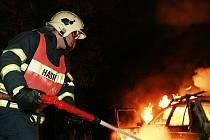Zasahující hasič při požáru vozidla.