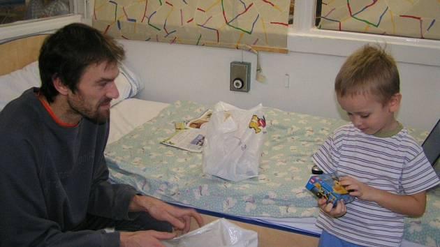 Věroslav Sucharda předává dárek malému chlapci.