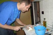 Basketbalista David Machač při své kuchařské práci.