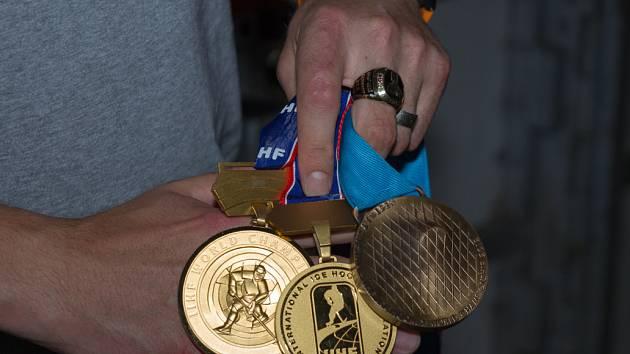 HOKEJOVÉ SKALPY Tomáše Mojžíše. Prsten pro Mistra světa 2010 a medaile z posledních třech let (zleva): zlato z MS v in-line hokeji 2012, zlato z MS v ledním hokeji 2010 a bronz z MS v ledním hokeji 2012.