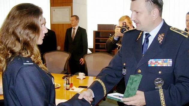 Policisté Kristína Bázlíková a Václav Kopeček za pomoci ručního hasicího přístroje ze služebního auta zabránili rozšíření požáru ve Velimi