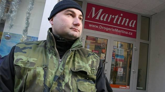 Pracovník ochranky hlídá vchod do jedné z prodejen sítě drogerií Martina.