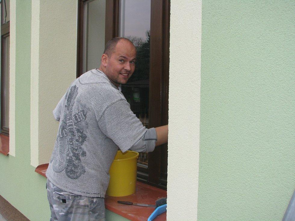 Poslední úpravy. Vlastně úklid. Starosta se pustil do mytí oken nově opraveného kulturního domu