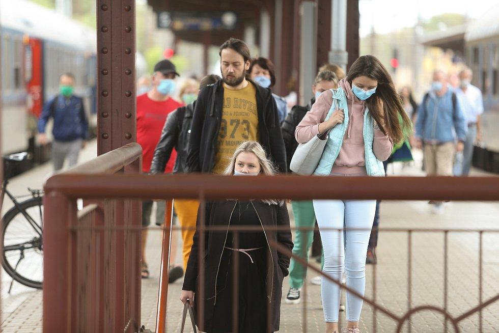 Lidé v rouškách na vlakovém nádraží v Kolíně.
