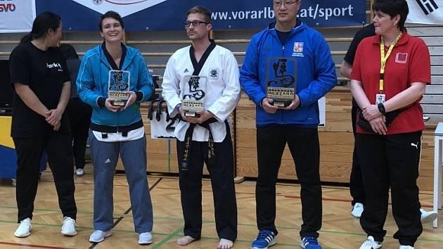 Mistr Lee (druhý zprava) přebírá trofej pro vítězný tým.