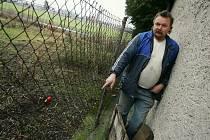 Majitel dogy ukazuje místo, kudy se pes dostal na sousedův pozemek. Mezi podezdívkou a plotem byla před tragédií jen přibližně dvoucentimetrová skulina.
