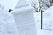 """Vrbčanská zvonice vykutaná z hromady sněhu u domu čp. 164 ve Vrbčanech. Pracovními nástroji byla nejprve lopata, potom  zednická lžíce a špachtle. Již třetí den byla sněhová stavba nakloněná. """"Asi jsem někde udělala chybu,"""" říká Jana Svobodová."""
