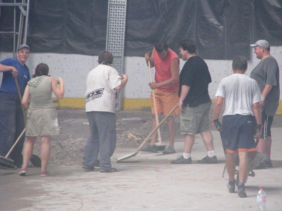 Úklidové práce uvnitř zimního stadionu.