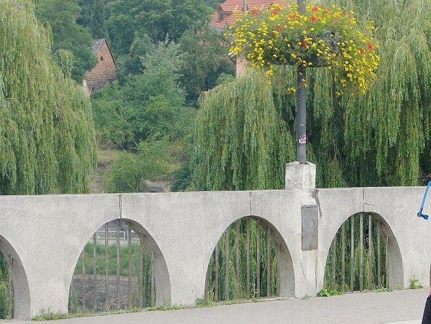 Muž, který chtěl skočit, seděl na kamenném zábradlí starého mostu.