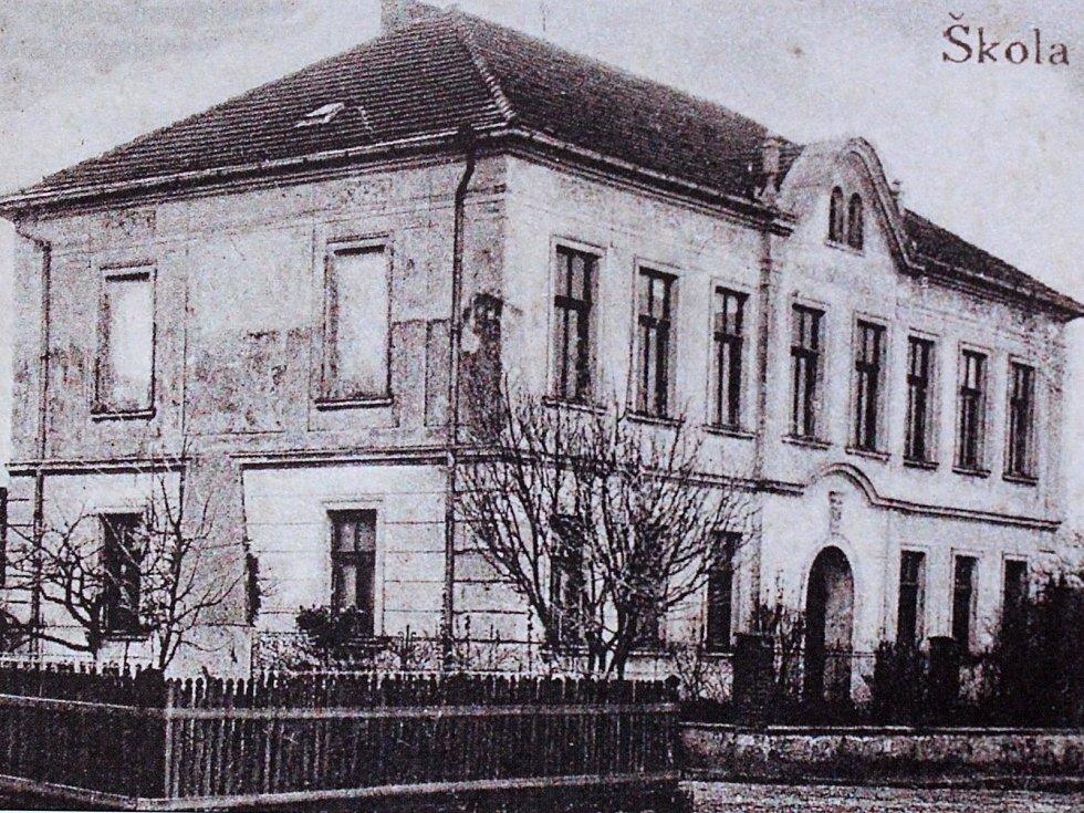 Na fotografii je zachycena pohlednice se školou a památníkem v Hradešíně kolem roku 1927.