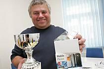 Petr Peška s vítězným pohárem a mobilním telefonem.