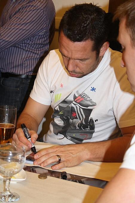 Pavel Horváth podepisuje kartičky.