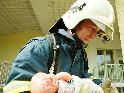 Dítě, byť tentokrát v podobě neživé panenky, má v rukou hasičů už nejnebezpečnější chvíle za sebou.