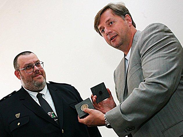 Jan Prošek přebírá z rukou hejtmana Petra Bendla medaili.